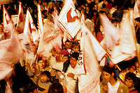 Crowds of people waving banners during a presidential election evening, Guatemala, Latin America.