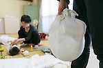 A woman holds a baby wrapped in cloth in a practice known as Ohinamaki on February 4, 2017, Tokyo, Japan. Parents wrap their babies to give them a feeling of security and help them with their physical development. The Japanese therapeutic method Otonamaki, which translates as ''adult wrapping'' is based on the practice of Ohinamaki to reduce stiffness and posture problems. The therapy  is monitored by a health care professional where participants are wrapped in a large piece of breathable cloth, like a sheet, for about 15 to 20 minutes. (Photo by Rodrigo Reyes Marin/AFLO)