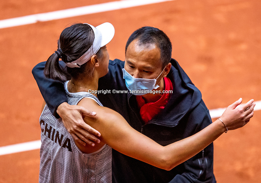 Den Bosch, The Netherlands, April 16, 2021,    Maaspoort, Billy Jean King Cup  Netherlands -  China , seccond day first match:   Xiyu Wang (CHN) celebrates with captain Shuo Liu (CHN) she puts China in a 1-2 lead by defeating Lesley Pattinama-Kerkhove (NED)<br /> Photo: Tennisimages/Henk Koster