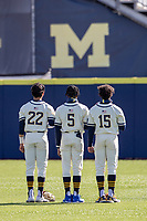 Michigan outfielders Tito Flores (22), Christian Bullock (5) and Clark Elliott (15) stand for the national anthem before the NCAA baseball game against the Illinois Fighting Illini at Fisher Stadium on March 19, 2021 in Ann Arbor, Michigan. Illinois won the game 7-4. (Andrew Woolley/Four Seam Images)