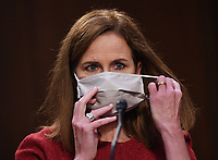 Judge Amy Coney Barrett removes her face mask when she returns from break as she appears before the Senate Judiciary Committee on day two of her confirmation hearings to become an Associate Justice of the U.S. Supreme Court, on Capitol Hill in Washington, DC on Tuesday, October 13, 2020. The hearings are expected to last four days. If confirmed, Barrett will replace Justice Ruth Bader Ginsburg, who died last month.    <br /> Credit: Kevin Dietsch / Pool via CNP /MediaPunch<br /> CAP/MPI/RS<br /> ©RS/MPI/Capital Pictures