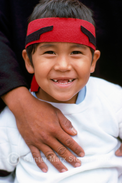 Happy Young Native American Heiltsuk Indian Boy wearing Traditional Ceremonial Red Headband at Pow Wow, BC, British Columbia, Canada - Portrait with missing Front Teeth (No Model Release Available)
