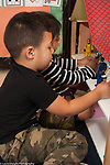 Education Preschool 3-4 year olds boy and girl playing with human figures dolls and dollhouse