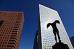 Sculpture by Igor Mitoraj with high rise office tower in background in La Défense. Paris. France