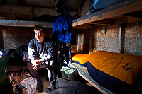 John Baker rest inside the musher sleep shack as Martin Buser sleeps in his bag during his 24 hour layover at the halfway point, Cripple checkpoint, during teh 2010 Iditarod, Interior Alaska