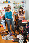 Mother arguing with teenage daughter, age 16, over condition of messy bedroom
