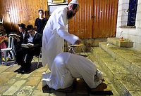 """An ultra-Orthodox Jew bows down as he is symbolically beaten during the """"Malkot"""" ceremony in a covered section of the Western Wall in Jerusalem's Old City shortly before the start of Yom Kippur September 15, 2002 in Jerusalem, Israel. The ceremony represents punishment for sins and is performed while reciting prayers for forgiveness ahead of Judaism's holiest day, the Day of Atonement, which begins at sunset on Sunday September 15 and ends at the same time the following evening."""