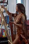 Beautiful young woman sumi-e artist with an easel painting half nude in comfort of her home studio wearing just a sheer robe over her naked body Image © MaximImages, License at https://www.maximimages.com