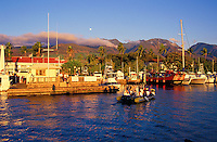 Lahaina Harbor at sunset with a full moon rising above the West Maui Mountains.