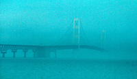 The Mackinac Bridge is obscured by fog rolling through the Straits of Mackinac where Lake Huron and Lake Michigan meet