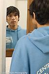 Teenage boy 16 years old looking at self in mirror in bathroom closeup vertical