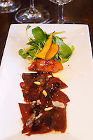 Carpaccio raw marinated beef with pine nuts olive oil balsamic vinegar and mache lettuce, red yellow bell pepper bellpepper fried pumpkin chips on a white plate. served to a guest with glass of water and wine The O'Farrell Restaurant, Acassuso, Buenos Aires Argentina, South America