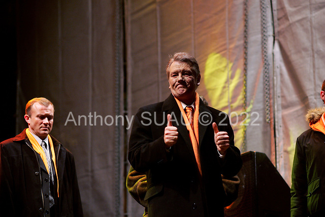"""Kiev, Ukraine.December 26, 2004..Opposition candidate Viktor Yushchenko takes the stage on Maidan Independence Square as thousands of Orange flag waving supporters rally to his side. Election polls show him in a strong lead just hours after the polling stations close. He is joined on stage by his wife Kathy, two children and his political partner Yulia Timoshenko. ..The first round of voting was considered fraudulent when the ruling president Viktor Yahukovich won and the opposition candidate Viktor Yushchenko lost. ..Several hundred thousand Ukrainians took to the streets of Kiev and held daily rallies on Maidan Independence Square. The protests lasted nearly a month before the first vote was declared invalid and a new round of elections held on December 26, 2004. ..The demonstrations would come to be known as the """"Orange Revolution"""" after the color of the opposition party."""