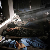 Refugees sleep in an abandoned building where they squat. Patras is home to about 3,000 illegal immigrants. Most of them are Afghans, although there are also some Iranians and Uzbeks. They stop in Patras to try and find passage to various European destinations by hiding in ships, containers and trucks parked in the port. If they are lucky they will make it to their destination. Many of them live in shacks made from cartons, plastic and wood they found on the beach. To shelter from the cold they also squat in abandoned buildings, living without water and electricity. The living conditions are inhumane and unhygienic.
