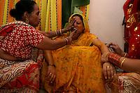 06.12.2008 Delhi(Haryana)<br /> <br /> Women of the family putting yellow oil on the body of the bride.<br /> <br /> Femmes de la famille de la mariée mettant de l'huile jaune sur le corps de la mariée;