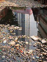 High rise Building reflecting in a waterway filled with rubbish and plastic in Manila, Philippines