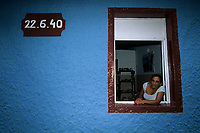 woman at the window of her house, Fernando de Noronha National marine sanctuary, Pernambuco, Brazil, South Atlantic Ocean