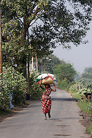 A woman walks along a rural road carrying bags on her head.<br /> <br /> To license this image, please contact the National Geographic Creative Collection:<br /> <br /> Image ID: 1925730 <br />  <br /> Email: natgeocreative@ngs.org<br /> <br /> Telephone: 202 857 7537 / Toll Free 800 434 2244<br /> <br /> National Geographic Creative<br /> 1145 17th St NW, Washington DC 20036