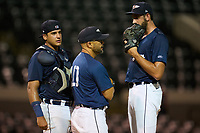 Lakeland Flying Tigers pitching coach Carlos Bohorquez talks with catcher Eduardo Valencia  (37) and pitcher Ted Stuka (24) during a game against the Jupiter Hammerheads on July 30, 2021 at Joker Marchant Stadium in Lakeland, Florida.  (Mike Janes/Four Seam Images)