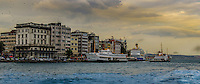 Fine Art Landscape Photograph. The Bosphorus Strait in Istanbul, Turkey. The dramatic lighting on the buildings and the birds flying overhead create the mood of this print. <br /> Everything seems in motion from the waves, to the birds, and the clouds.