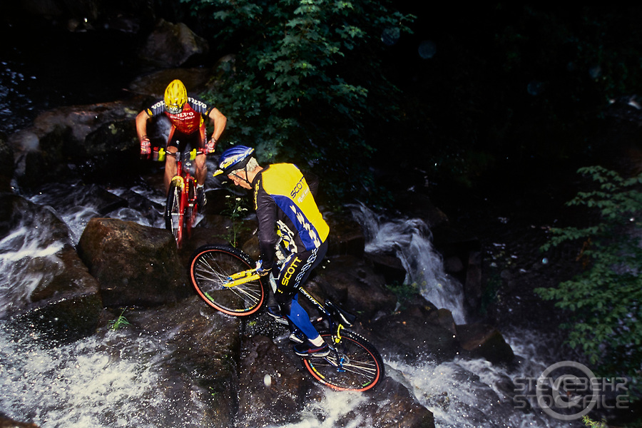 20112-10111-02A  Martyn Ashton and Martyn Hawyes riding trials mountain bikes  up a waterfall.  Scott and Volvo Cannondale.  Surrey, Mid 1990's.