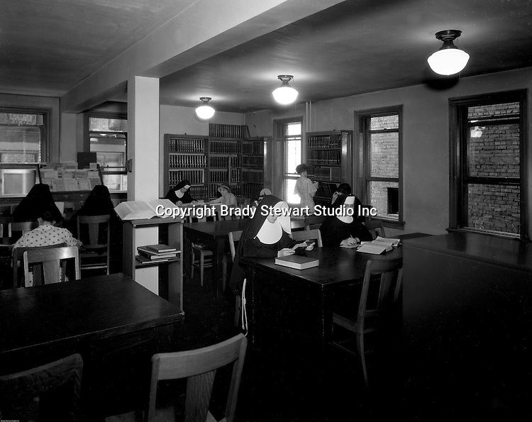 Pittsburgh PA: Catholic Sisters and students in the Duquesne University library.<br />