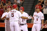 Chris Iannetta #17, Mike Trout #27, and Kendrys Morales #8, greet Albert Pujols #5 of the Los Angeles Angels after Pujols home run during a game against the Cleveland Indians at Angel Stadium on August 14, 2012 in Anaheim, California. Los Angeles defeated Cleveland 9-6. (Larry Goren/Four Seam Images)