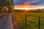 Great Smoky Mountains National Park, TN/NC: Country road and fence line with evening sunburst and clearing storm in Cades Cove, early spring