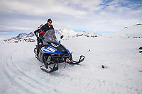 Transporting people and equipment with snowmobile to the ice field, only when the hard winter slowly subsides, are the ice-cold waters suitable for divers who can dive around a iceberg that floats in crystal-clear water, Tasiilaq, Greenland, North Atlantic Ocean