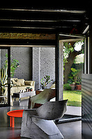 Two grey Tara Britton hemp moulded chairs are set around a low red table. Open glass doors lead to a living room on one side and to the garden on the other.