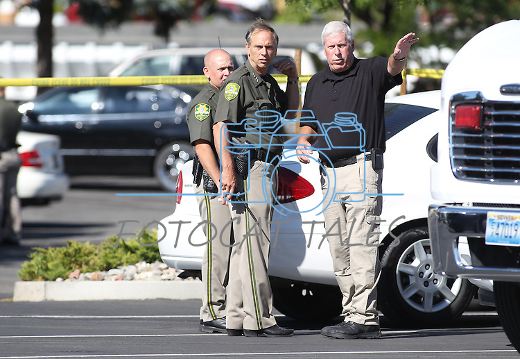 Carson City Sheriff Ken Furlong, center, and Undersheriff Steve Albertsen, right, work on the scene of a shooting in an IHop restaurant in Carson City, Nev., on Tuesday, Sept. 6, 2011. Early reports had eight people shot and four killed.  (AP Photo/Cathleen Allison)