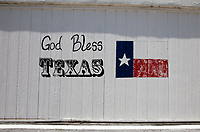 """View of a iconic """"God Bless Texas"""" mural with Texas Flag painted on the side of a building in the Texas Hill Country."""