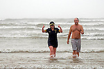 """Female swimmer wearing Airline Pilot outfit as she leaves the sea at the annual Boxing Day """"Walrus Dip"""" at Cefn Sidn beach in Pembrey near Llanelli today.."""
