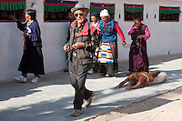 Bodhnath, Nepal.  A Buddhist Devotee Seeks Merit, Blessings, and Forgiveness by Circling the Stupa in a series of Prostrations.  Others Circumambulate the Stupa on Foot, always in a Clockwise Direction.