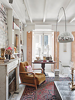 An Arco floor lamp stands in front of an antique mahogany occasional table with a pair of marble heads