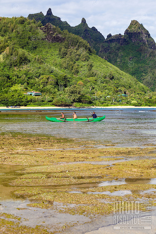 Men paddle an outrigger canoe towards Tunnels Beach, Ha'ena, Kaua'i.