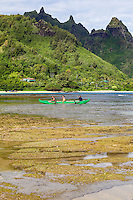 Men paddle an outrigger canoe towards Tunnels Beach, Ha'ena, Kaua'i.