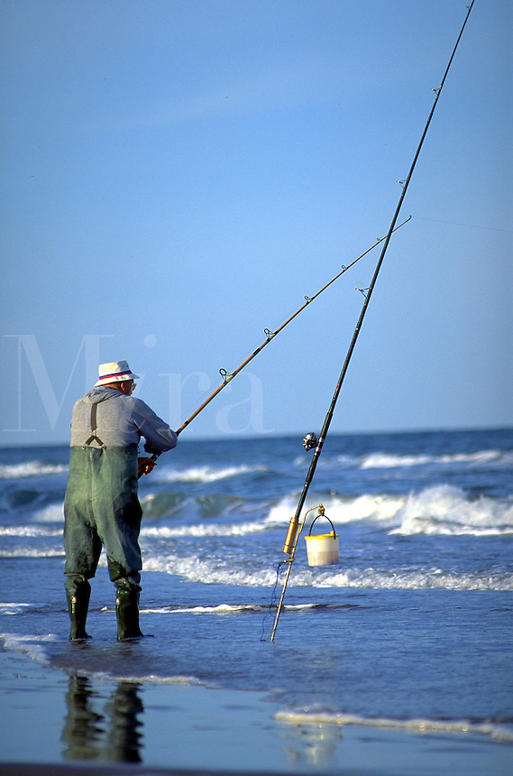 old man surf fishing on a beach. United States.