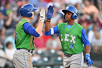Right fielder Khalil Lee (9) of the Lexington Legends is congratulated by Kort Peterson (8) after his second-inning home in a game against the Columbia Fireflies on Saturday, April 22, 2017, at Spirit Communications Park in Columbia, South Carolina. Lexington won, 4-0. (Tom Priddy/Four Seam Images)