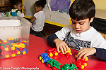 Education Preschool 3 year olds boy making a circle of plastic cars