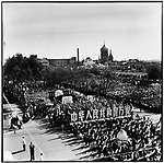 """Marchers in Harbin during the National Day parade carry large wooden characters that read, """"Long live the People's Republic of China,"""" and banners with profiles of Marx, Engels, Lenin, and Stalin followed by one of Mao Zedong. The Russian Orthodox cathedral of St. Sophia is visible in the background. 1 October 1963."""