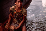 Kuching; Sarawak; Borneo; Malaysia; A blur image of a remarkable young man unloading coconuts two by two from a boat on the Sarawak River (Sungai Sarawak) for the markets of Kuching