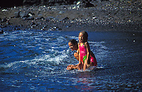 Young girls playing at a black sand beach, Kona, Big Island