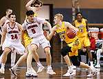 SIOUX FALLS, SD - MARCH 8: Sam Griesel #5 of the North Dakota State Bison drives toward Kruz Perrott-Hunt #5 of the South Dakota Coyotes during the Summit League Basketball Tournament at the Sanford Pentagon in Sioux Falls, SD. (Photo by Richard Carlson/Inertia)