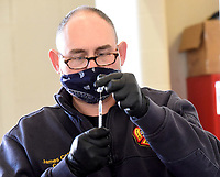 BENTONVILLE VACCINATION DRIVE-THROUGH<br />Capt. James Cooper with the Bentonville Fire Department prepares doses of  Pfizer covid-19 vaccine on Saturday Feb. 20 2021 at the main fire station in downtown Bentonville. The fire department, city of Bentonville and Northwest Health hosted a drive-through vaccination clinic for Bentonville residents who preregistered for the event. Firefighters, paramedics and nursing students administered 500 doses, said Brent Boydston, Bentonville fire chief. Each will receive their second dose at a similar drive-through event on March 13 at the station, Boydston said. People eligible to receive the vaccine were residents 70 and older, and also teachers, school staff and child care workers. Some 90 percent of people vaccinated on Saturday were residents 70 and older, said Debbie Griffin, community relations director with the city. Go to nwaonline.com/210221Daily/ to see more photos.<br />(NWA Democrat-Gazette)