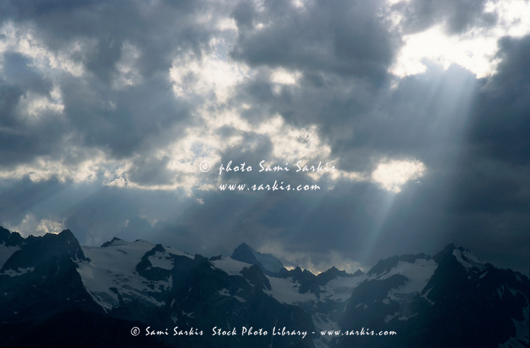Sunbeams playing over the Barre des Ecrins and La Meije mountains in the French Alps, France.