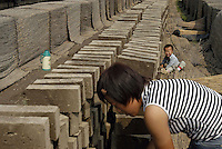 A woman dries the clay bricks in the sun while her son plays nearby at a brick factory in Bazhou, Hebei province, China..04-SEP-04