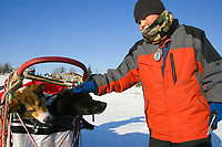 Nikolai resident Greg Tony pets *Burt* one of Ramy Brooks' dogs  as it sits in the sled bag at the Nikolai checkpoint on Tuesday
