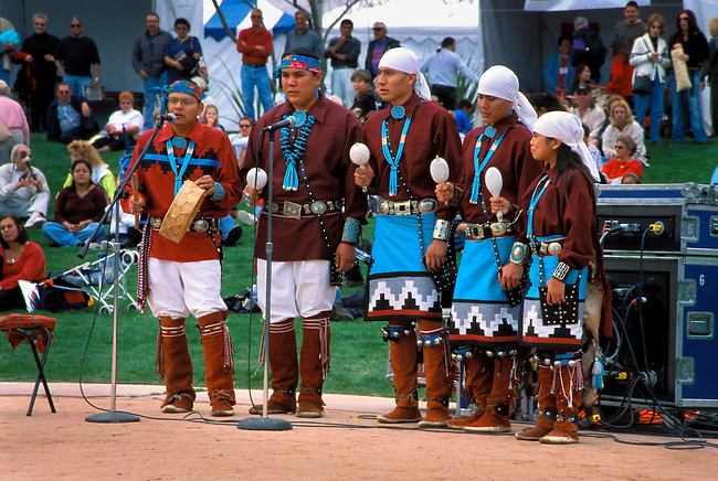 Group of Navajo singers dressed in traditional clothing and moccasins sing traditional songs while shaking gourd rattles and a drum