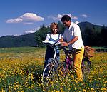 Paar mit Fahrraedern und Landkarte stehen in einer Blumenwiese | couple with bicycles and map standing in a flower meadow